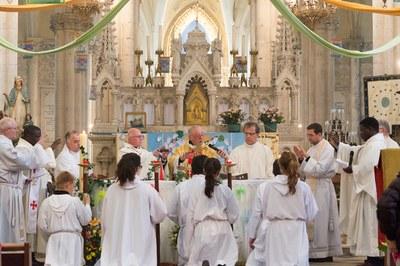 Prêtres levant la main droite en désignant le Corps et le Sang du Christ