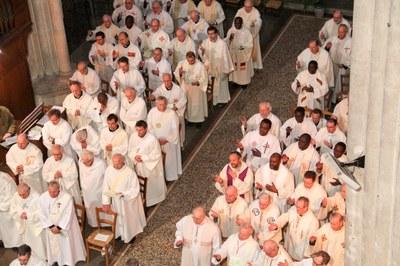 Prêtres lèvent la main droite en désignant le corps et le sang du Christ